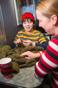Max Lanzkron-Tamarazo, 12, chose to learn to knit as part of his homeschooling. He works on his bar mitzvah tallit as he chats with his mom, Lisa. (Photo by Brett Mountain)