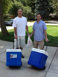 Larry Oleinick and Ken Levy with the cooler that they pull around Hart Plaza filled with sandwiches in the summer.