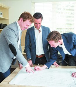 Tyler Ross, Michael Colman and David Colman look over development plans for ROCO real estate. (Photos by Brett Mountain)