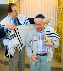 Isaak Trabsky of Oak Park gets assistance with his tallit from Cantor Greenbaum.