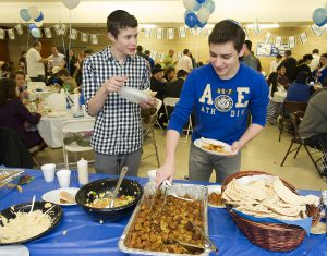 Isaac Wolfe of West Bloomfield and Ziv Brodie of Southfield, both juniors at Akiva, get some Israeli food at the school's annual Yom HaAtzmaut celebration.
