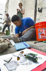 Lead researcher Shawn Fields of Detroit digs out artifacts from under the paving stones behind the bar.