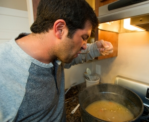 Josh Fishman checks the food while Jordan Rosenbaum stirs soup on the top of the range.