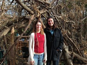 Sky and David Brown in front of their sukkah built from twigs and branches