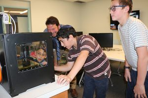 Watching an object printed layer by layer on Hillel Day School's 3D printer: seventh-graders Scott Siegel (in window), Jacob Banooni and Alex Aisner with Trevett Allen, director of innovation.