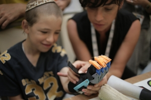 Israeli Nathanel is fitted with the prosthetic hand designed and 3D printed by a team at the Tikkun Olam Make-a-Thon this summer in Nazareth.