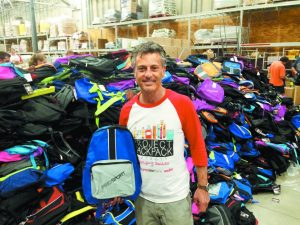 Attorney Mike Morse in front of a growing pile of backpacks