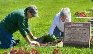 Jay and Sharon Daitch of West Bloomfield pull weeds from a grave.