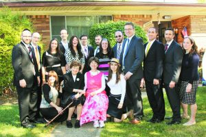 Aviva Cohen, widow of Rabbi Eliezer Cohen, center in pink, surrounded by her family