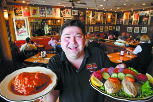 Ziggy Gruber, owner of Kenny & Ziggy's Deli, holds the Hungarian Stuffed Cabbage (left) and Gefilte Fish with Horseradish at his restaurant Kenny & Ziggy's New York Delicatessen Restaurant Friday, Aug. 27, 2010, in Houston. The restaurant prepares tons of special foods for take away for Rosh Hashana and other Jewish holidays. ( Michael Paulsen / Houston Chronicle )