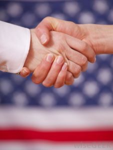 two-people-shaking-hands-near-american-flag-226x300