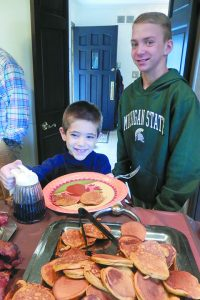Max Petry of Bartlett, Ill., watches Nate Gold of Northville help himself to his first pancakes of the morning.
