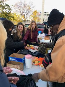 Bree Gross of Franklin and Emma Sable of Bloomfield Hills distribute socks, gloves and hand warmers to the homeless at Hart Plaza
