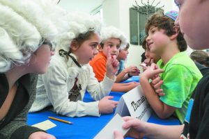 Jessica Primus, 8, aka Thomas Jefferson, explains her group's policy positions to Asher Stein, 6. (Credit, Michael Fried)