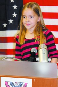Nina Olson, 8, takes the podium during the election. (Credit, Alison Reingold)
