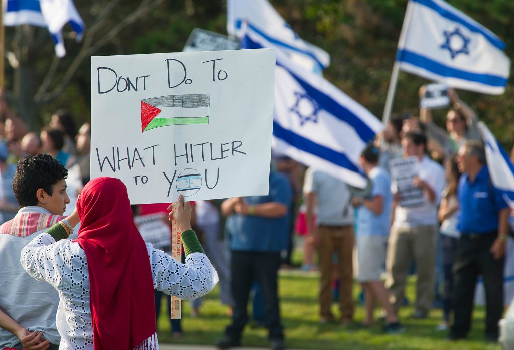 A Palestinian protestor holds up a sign for the Jewish protestors to see.