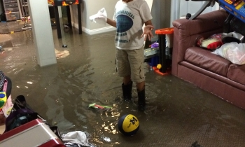 Spencer Cherrin of Huntington Woods stands in his flooded basement. Damaged prayer books there will be taken to Congregation Beth Shalom for proper burial.