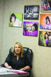 """Cathy Eisenberg of Child & Parent Services, a nonprofit private adoption agency in Bingham Farms, with Marla Must's """"forever family"""" portraits on her office wall"""
