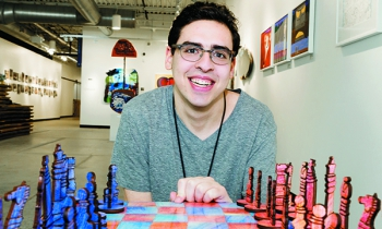 Artist David Kole sits in the Soul Center's Rissman Gallery at the chess set he designed and made.