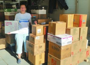 Lori Lasday with the packed boxes of materials from Beth Israel synagogue.